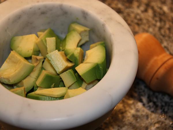 Avocado nel mortaio per salsa guacamole